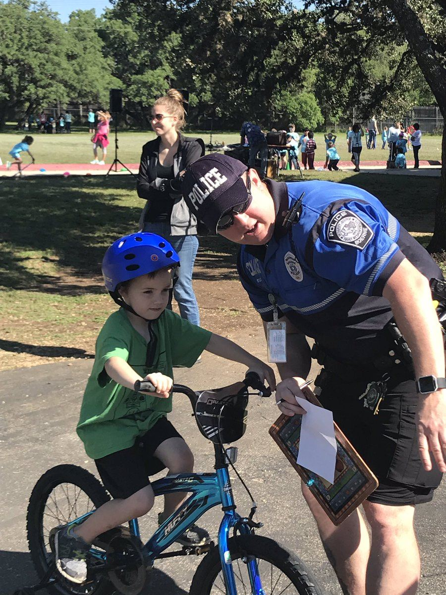 Police Officer helping student on bicycle